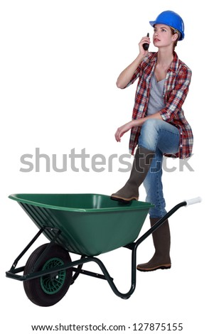 Tradeswoman speaking into a walkie-talkie and propping her foot up on a wheelbarrow - stock photo