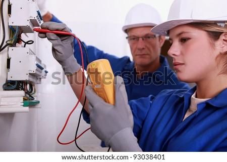 Tradeswoman using a multimeter - stock photo