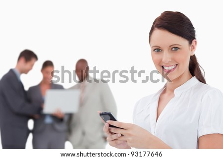 Tradeswoman with cellphone and co-workers behind her against a white background - stock photo