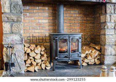 Tradional Wood Burning Stove in a Brick Fireplace - stock photo