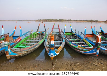 Tradition of local boat on Amarapura lake with U-Bein bridge background