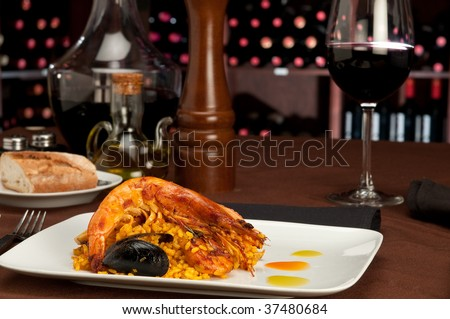 Tradition Seafood Spanish Paella in a restaurant table setting and wine cellar in the background. - stock photo