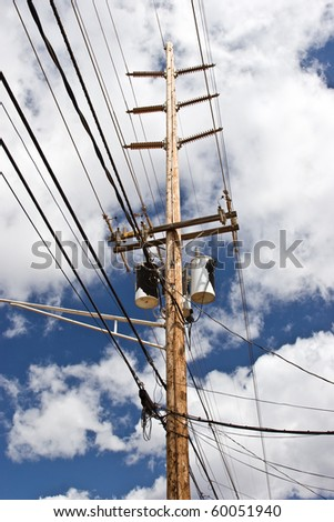 Traditional above ground high voltage pole and lines with transformer boxes - stock photo