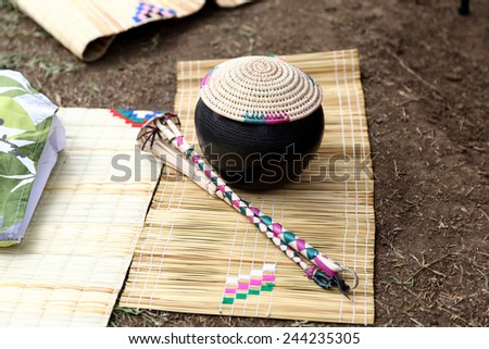 Traditional African calabash with straw cover and drinking tools on grass mat - stock photo