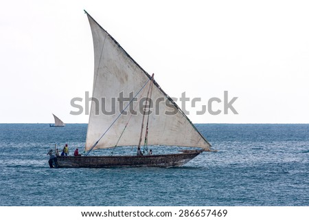 traditional african dhow sailing vessel with full sail to the wind in the open blue ocean - stock photo