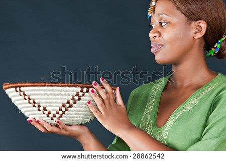 traditional african woman looking at  botswana basket, dark background - stock photo