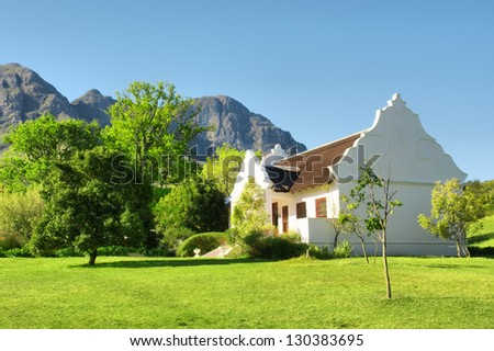Traditional Afrikaner house against mountains. Shot in Helderberg Mountains Nature Reserve, near Somerset West/Cape Town, Western Cape, South Africa. - stock photo