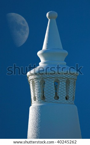 Traditional Algarve chimney with the moon behind - stock photo