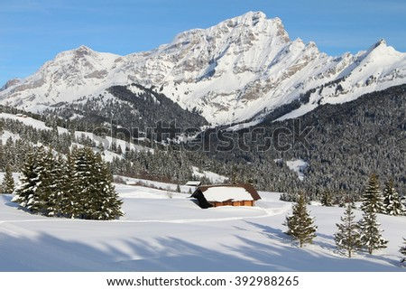 Traditional alpine cabin in the mountains of the Swiss Alps, Switzerland with a view of a beautiful mountain. - stock photo