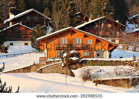 Traditional alpine cabins in the mountains of the Swiss Alps, Switzerland in the golden sunset light. - stock photo