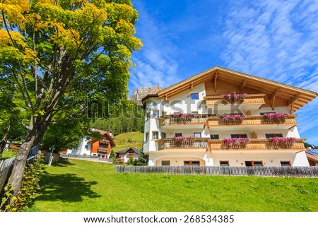Traditional alpine houses on green meadow in summer landscape of Dolomites Mountains, Italy - stock photo
