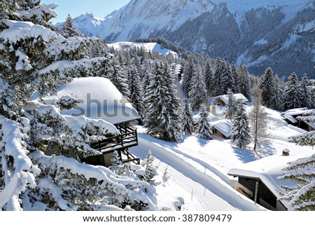 Traditional alpine huts in a snowy, wintery setting in the Swiss Alps. - stock photo