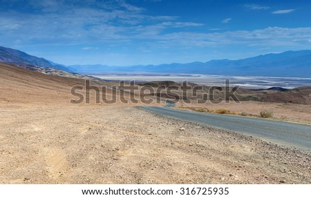 Traditional American Scenic Long Highway in the Mountains of Death Valley National Park in California, USA. Horizontal Image - stock photo