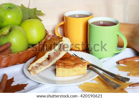 Traditional Apple Pie dessert, yeast dough, brown sugar, cinnamon, raisins, decorated with green apples, dried roses,  tea and autumn foliage on light pastel background, close up view, selective focus