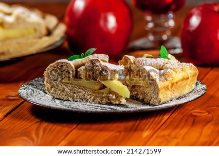 Traditional apple pie on black plate on wood table