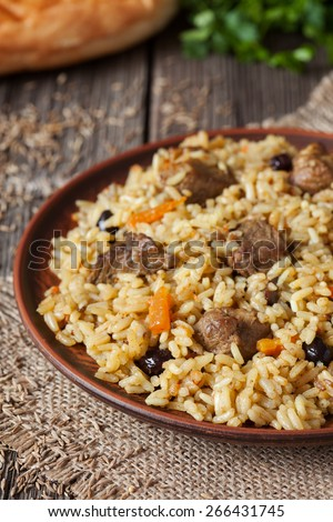 Traditional arabic spicy rice food with meat, onion carrot and garlic. Served with fresh bread and vegetables on vintage dish on wooden background