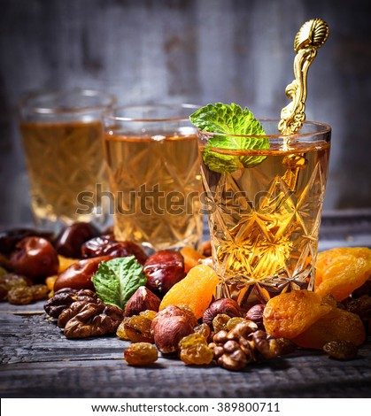 Traditional arabic tea and dry fruits. Selective focus, toned, square image - stock photo