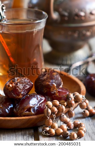 Traditional arabic tea with wood rosary and dry madjool dates . Selective focus. - stock photo