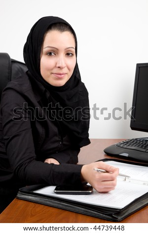Traditional Arabic young woman at the office with phone and documents - stock photo
