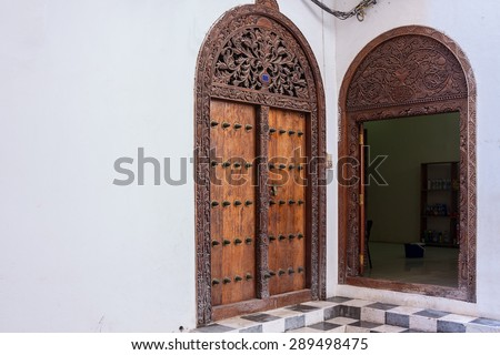 traditional Arabic Zanzibar doorway ornately carved showing the interior and exterior of this entrance. - stock photo