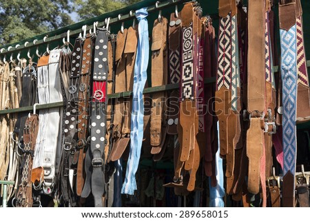Traditional Argentinean leather gaucho belts and cinchs hanging on for sale on a fair in Rosario city, Argentina