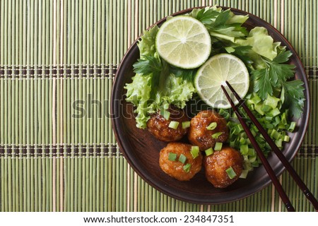 Traditional Asian fish balls with salad and chopsticks on a bamboo table close-up. top view of a horizontal  - stock photo
