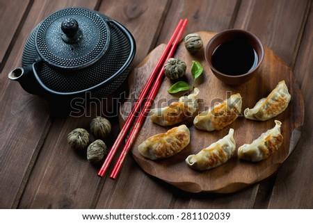 Traditional asian pan fried gyoza dumplings with a dip sauce - stock photo