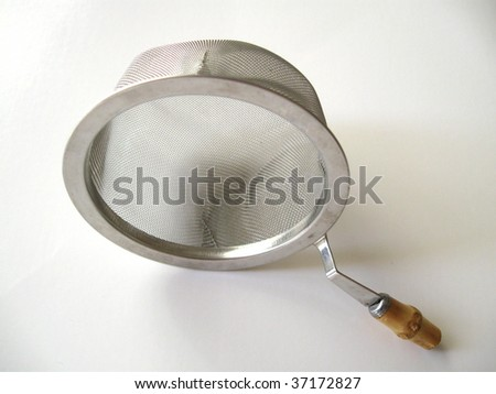 Traditional Asian tea strainer with wooden handle isolated on white background.