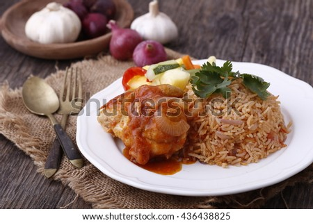 traditional asian Tomato nasi rice with fried kunyit roasted chicken masak merah served on wooden table with ingredients in background