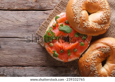 Traditional bagel with red fish and soft cheese on the table closeup. horizontal view from above  - stock photo