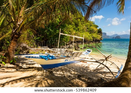 Traditional banca boat in the shade on the beach near Cudugnon Cave, El Nido, Palawan Island, Philippines
