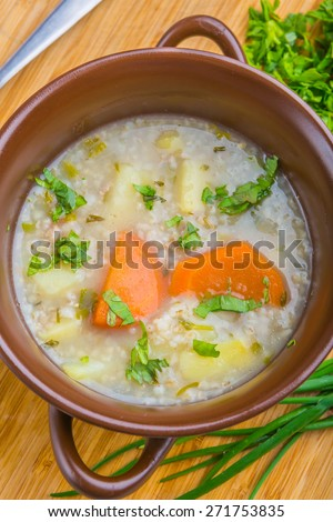 Traditional barley soup with parsley in a dark bowl