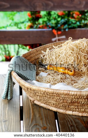 Traditional basket filled with tagliatelle - stock photo