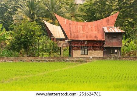 Traditional Batak house on Samosir island, Indonesia. Samosir is the largest island within an island and the fifth largest lake island in the world. - stock photo