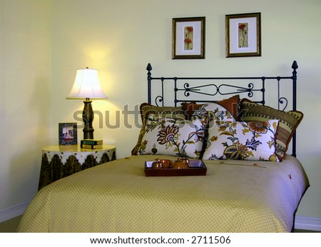 traditional bedroom with floral bedding and side table - stock photo