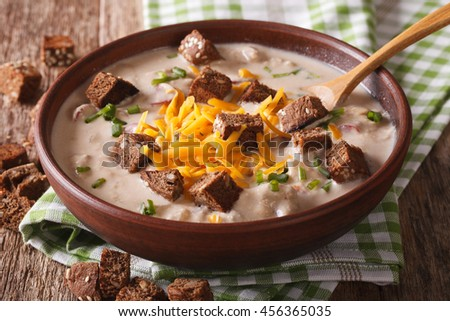 Traditional beer soup with bacon, cheddar cheese and croutons in a bowl close-up on the table. horizontal - stock photo