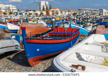 Traditional big blue fisherman boat with the red stripes on the shore of Doca Dos Pescadores in Setubal, Portugal.