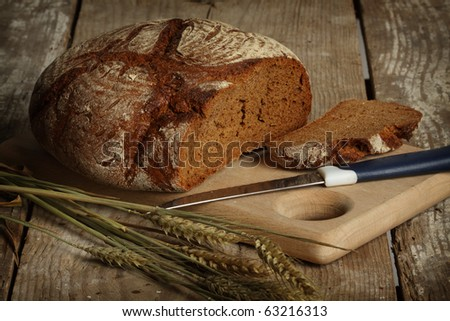 Traditional black rye-bread on vintage table - stock photo