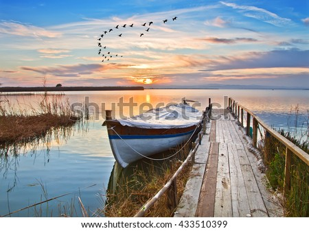 Traditional boat on the lake pier - stock photo