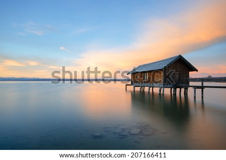 Traditional boathouse at lake Ammersee near Munich, Bavaria, Germany at sunrise. - stock photo