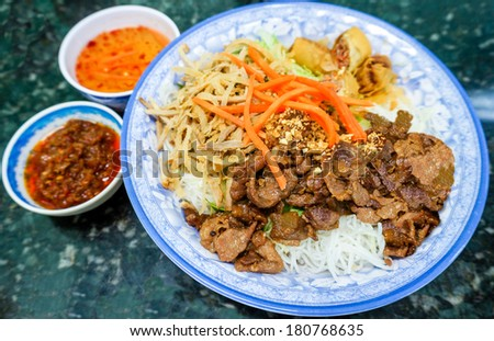 Traditional bowl of Vietnamese bun vermicelli rice stick noodle salad with charbroiled meat, shredded pork, deep fried spring rolls and pickled carrots served with mint leaves, peanuts and fish sauce. - stock photo