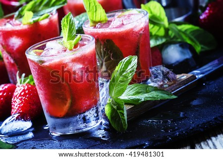 Traditional Brazilian alcoholic cocktail, strawberry caipirinha with Cachaca, sugar syrup, lime, mint, strawberries and crushed ice, black background, selective focus - stock photo