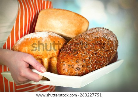 Traditional bread in female hands on wooden tray on light blurred background