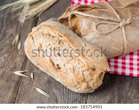 Traditional bread on old wooden table with red cloth - stock photo