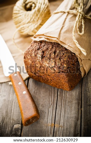 Traditional bread with seeds wrapped in paper on old wooden table