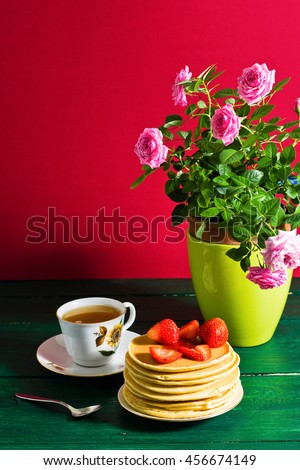 Traditional breakfast: pancakes with syrup and strawberry, green tea. Still life, served on green wooden table. - stock photo