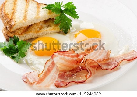 Traditional breakfast with bacon , fried eggs on white plate - stock photo