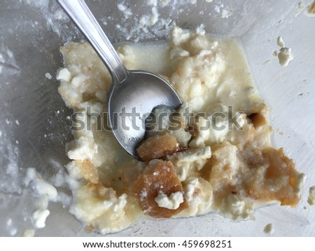 Traditional breakfast with cheese and bread in a clear bowl with a spoon / sop