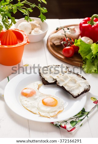Traditional breakfast with fried eggs, bread with cream cheese and fresh vegetables on white background. Selective focus