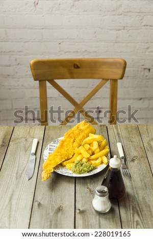 Traditional British takeaway meal of fish and chips with mushy peas on a newsprint plate